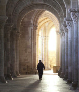 Priest Walking in a long corridor